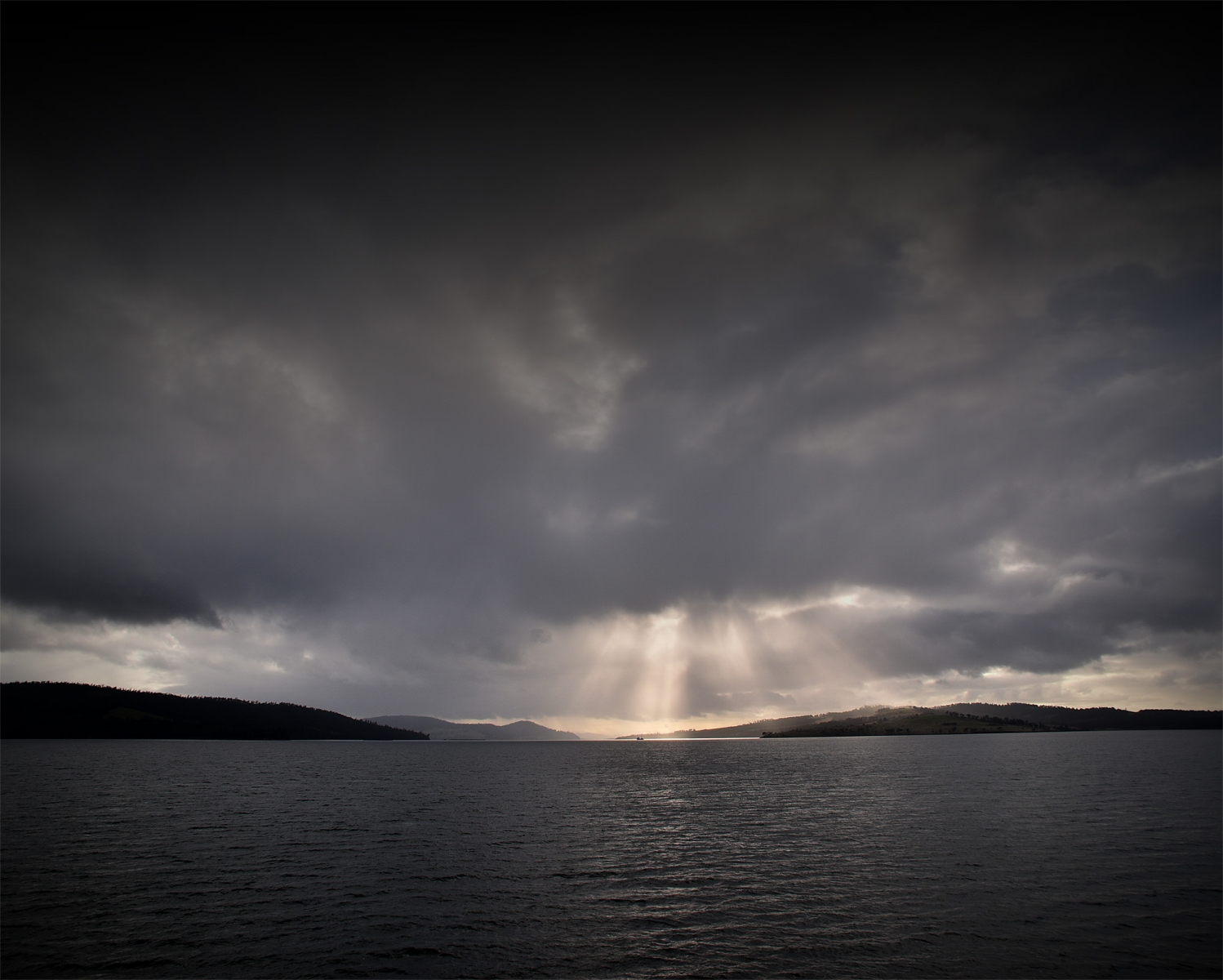 View of light breaking through clouds on the d'Entrecasteaux Channel, from the Bruny Island ferry.